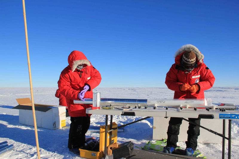 Zdjęcie przedstawia dwoje naukowców w czerwonych kurtkach, zabezpieczających zamknięty w specjalnym pojemniku podłużny rdzeń lodowy. W tle lodowy krajobraz.