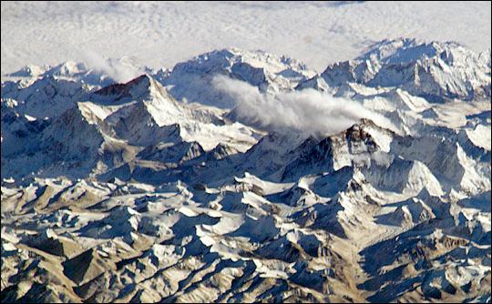 Ośnieżony i skryty w chmurach łańcuch górski.