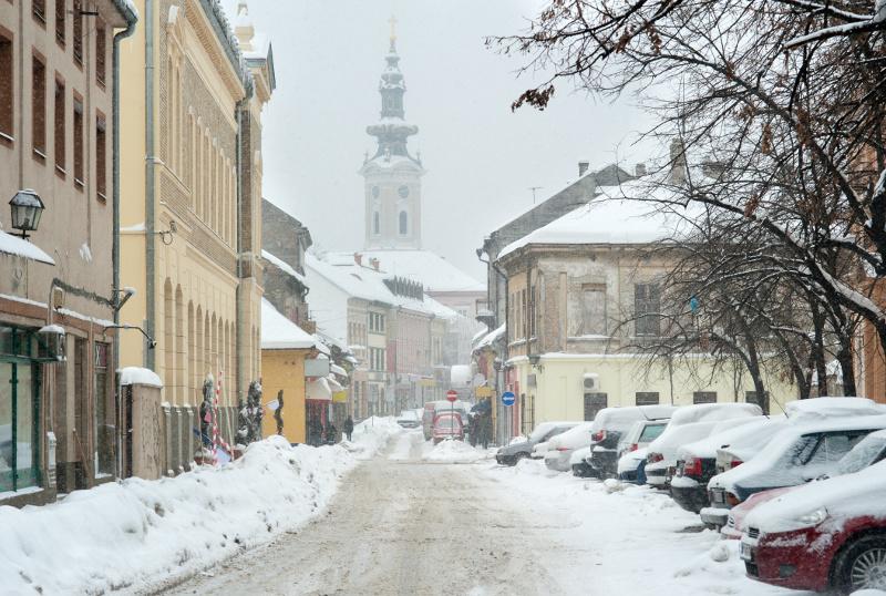 Zdjęcie przedstawiające miejską uliczkę podczas opadów śniegu.