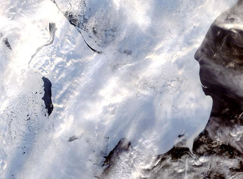 Zdjęcie przedstawia widzianą z góry, pękającą skorupę lodową (w szczelinach widoczne jest czarne morze), częściowo przesłoniętą chmurami.