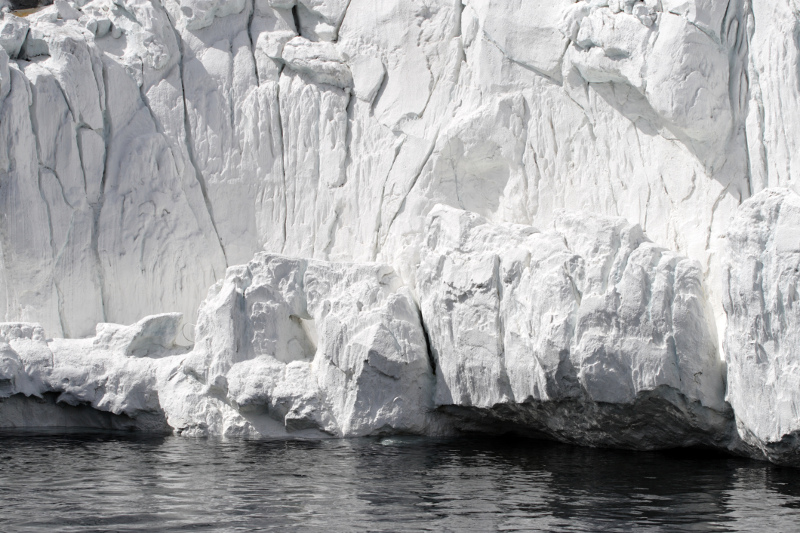 Zdjęcie przedstawia białą ścianę lodowca podcinaną przez morze