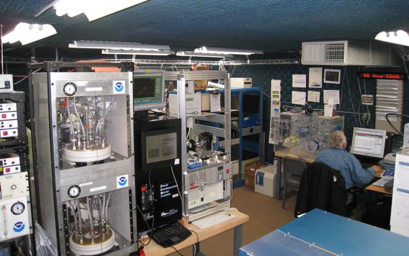 Zdjęcie przedstawia pokój pełen aparatury naukowej z rurkami i pudłami z elektroniką.
