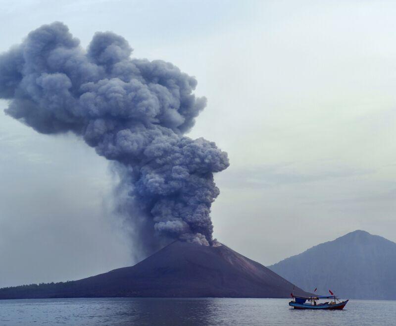 Zdjęcie przedstawia obficie dymiący wulkan na wyspie.