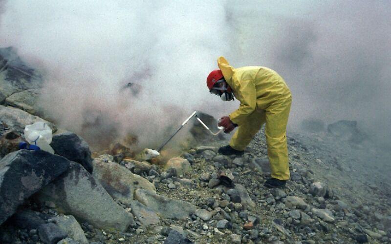 Zdjęcie przedstawia człowieka ubranego w kombinezon, wiercącego w skale