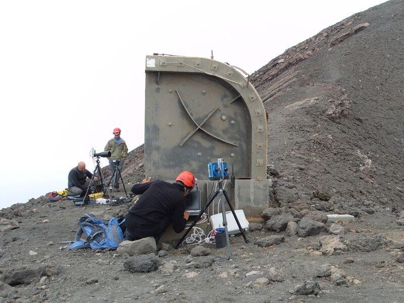 Zdjęcie przedstawia naukowców z kamerami i laptopami siedzących na zboczu wulkanu.