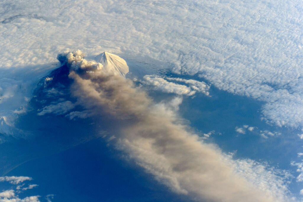 Zdjęcie przedstawia widziany z powietrza szczyt wulkanu, wypusszczający kłęby ciemnego dymu nad chmurami