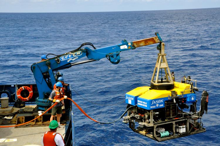 Zdjęcie przedstawia fragment statku i ludzi opuszzających do wody za pomoca dźwigu duże urządzenie