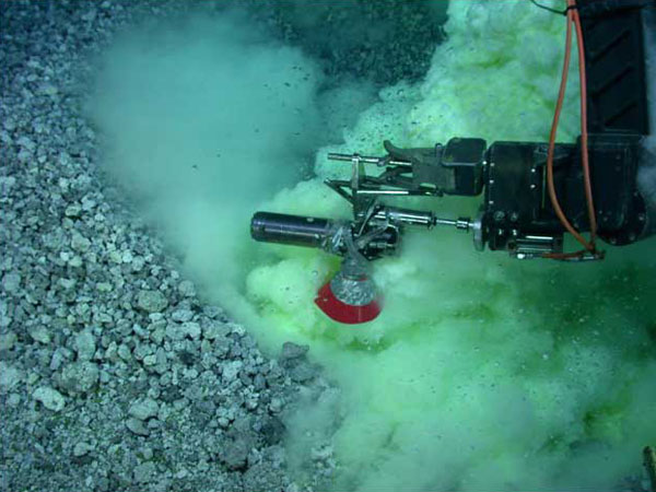 Zdjęcie przedstawia pobieranie próbek przez pojazd podwodny, widać mnóstwo bąbelków i robotyczne ramię
