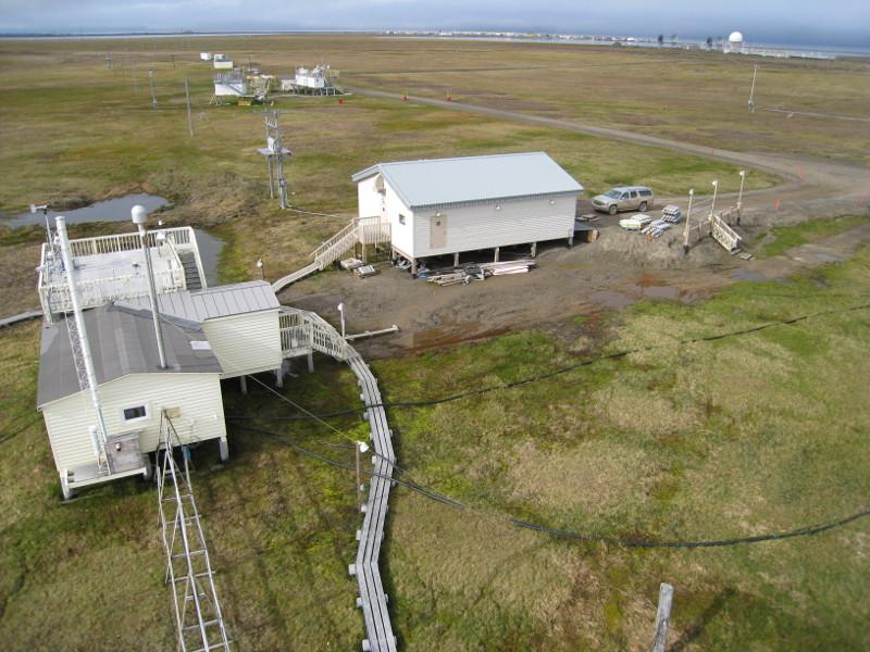 Zdjęcie przedstawia płaski obszar porośnięty rachityczną trawą i białe budynki z aparaturą naukową.