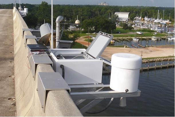 zdjęcie przedstawia obudowane urządzenia - w tym jedno o kształcie cylindrycznym - zamontowane na mostku nad wodą