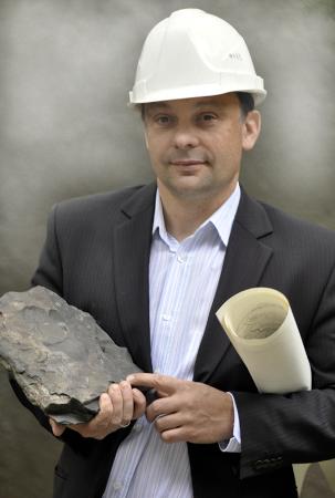 zdjęcie przedstawia mężczyznę w średnim wieku, w garniturze, kasku ochronnym, z rulonem pod pachą i kawałkiem skały w ręku.