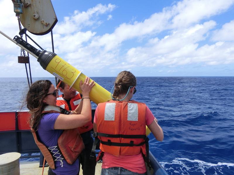 Zdjęcie przedstawia stojące na pokadzie statku dwie kobiety w pomarańczowych kamizelkach ratunkowych, trzymające żółty ctlinder długości ok. 120cm, zakończony czarną czapeczką z anteną.