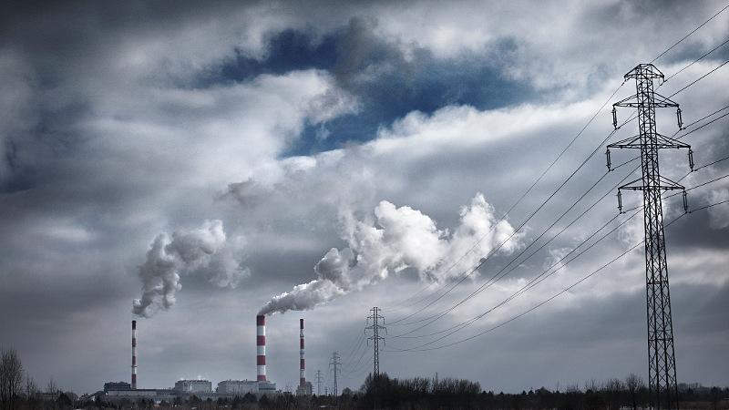 Zdjęcie przedstawia elektrownię z oddali, widoczne są trzy wysokie, cienkie kominy, dym mieszający się z chmurami i przewody elektryczne ze słupami po prawej stronie