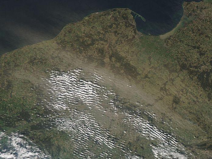 Satelitarne zdjęcie obszaru Polski. Widoczne niewielkie chmurki, ziemia w wielu miejscach przesłonięta żółtawą zasłoną pyłu.