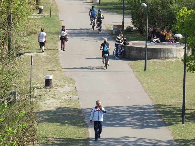 Gorący kwiecień: ludzie przechadzajcy się i jeżdżący na rowerach po nadrzecznej promenadzie.
