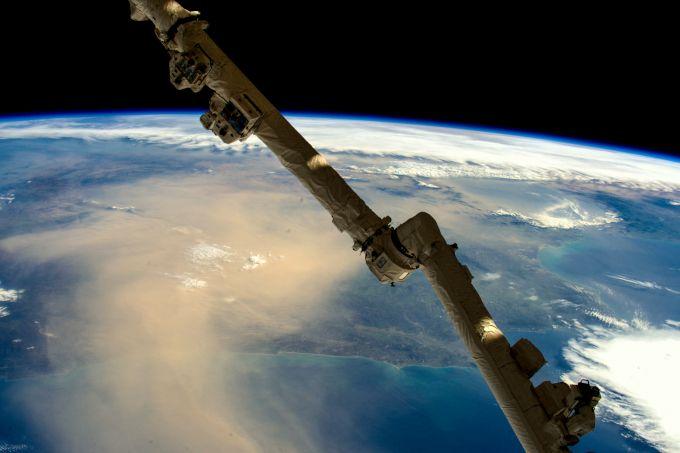 Ziemia widziana ze stacji kosmicznej: widoczny fragment globu w widoczną krzywizną, przykryy warstwą chmur i żółtawym, gęstym obłokiem pyłu.