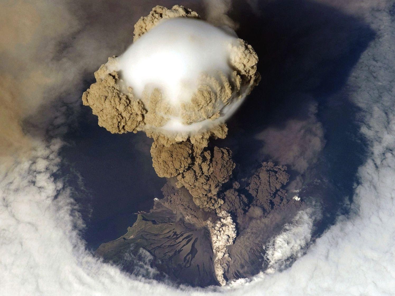 """Zdjęcie erupcji wulkanicznej zrobione z pokładu stacji kosmicznej. Widoczna wielka kolumna popiołów, na szczycie której powstała też chmurowa """"czapeczka""""."""