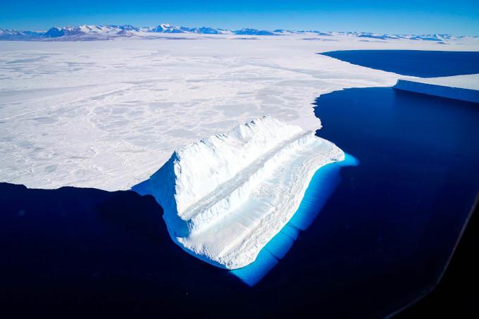 Góra lodowa i lód morski na powierzchni zatoki McMurdo w Antarktyce