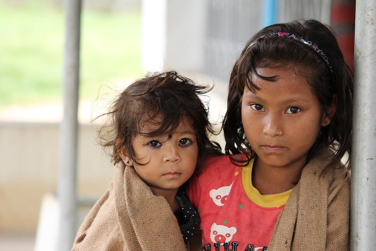 Dziewczynki z Nepalu otulone kocem, starsza trzyma młodszą na rękach.