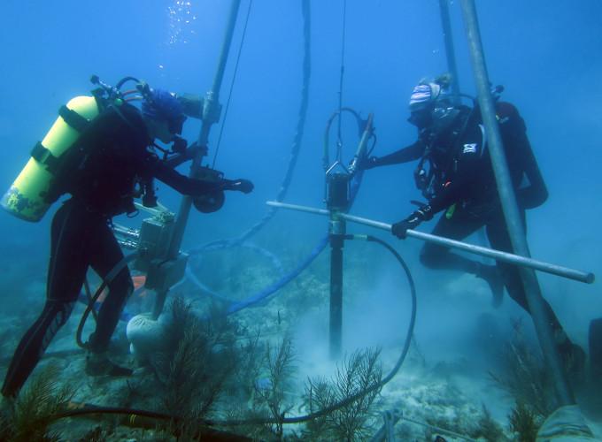 Zdjęcie: dwoje nurków z butlami tlenowymi obsługuje duże wiertło wbite w dno oceanu, zawieszone na wielkim, wbitym w podłoże trójnogu