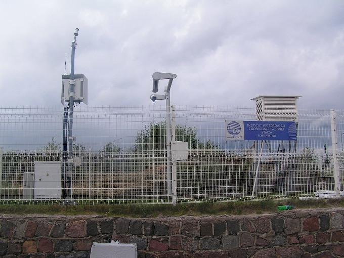 Zdjęcie stacji pomiarowej IMGW, widoczne są dwa urządzenia na masztach i skrzynka meteorologiczna ogrodzone białą siatką