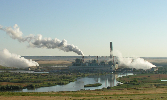 Zdjęcie: elektrownia węglowa w Wyoming, duża budowla przemysłowa z czterema niższymi i jednym wielkim kominem, stojąca na środku równiny, nad rzeką