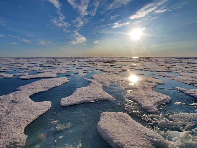 Zdjęcie: sadzawki wytopionej wody na powierzchni lodu morskiego w Arktyce. Widać białą powierzchnię lodu i niebieskie zagłębienia z wodą. Świeci Słońce.