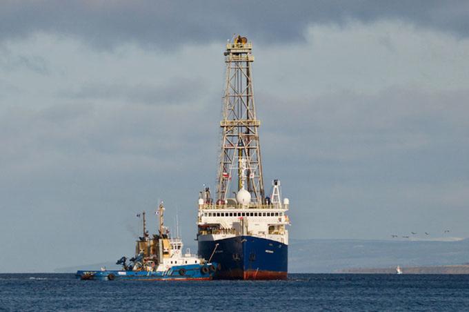 Zdjęcie:  statek badawczy JOIDES Resolution widziany od strony dziobu, nad kadłubem góruje ażurowa konstrukcja podtrzymująca wiertło.