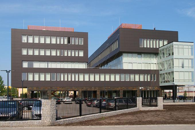 Zdjęcie: siedziba PGE w Bełchatowie. Nowoczesny budynek biurowy z proporcami z logo spółki.