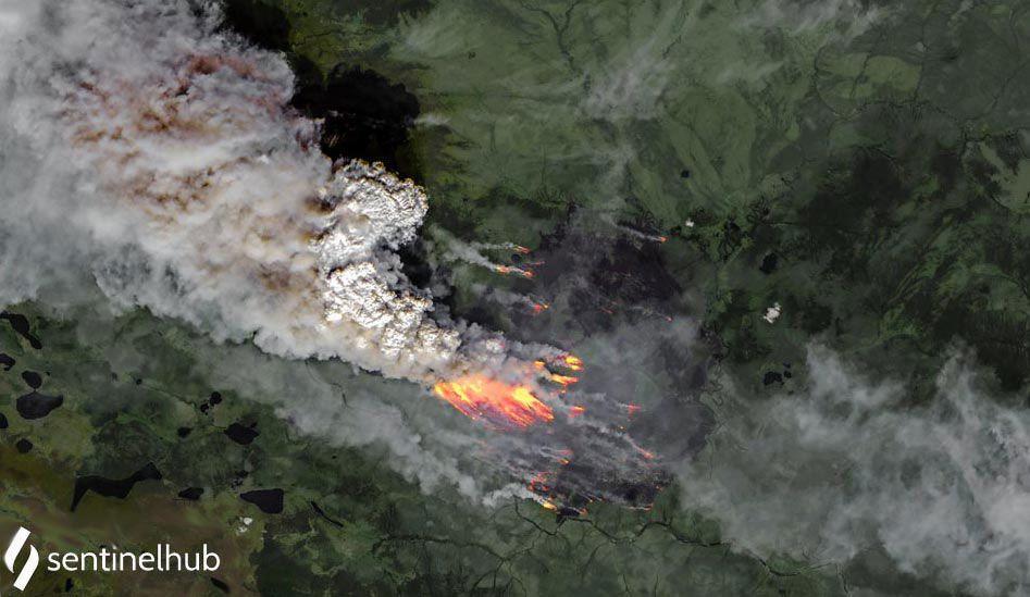 Zdjęcie satelitarne: pożar tajgi, widoczne plama ognia i wielkie kłęby dymu unoszące się wysoko w atmosferze.