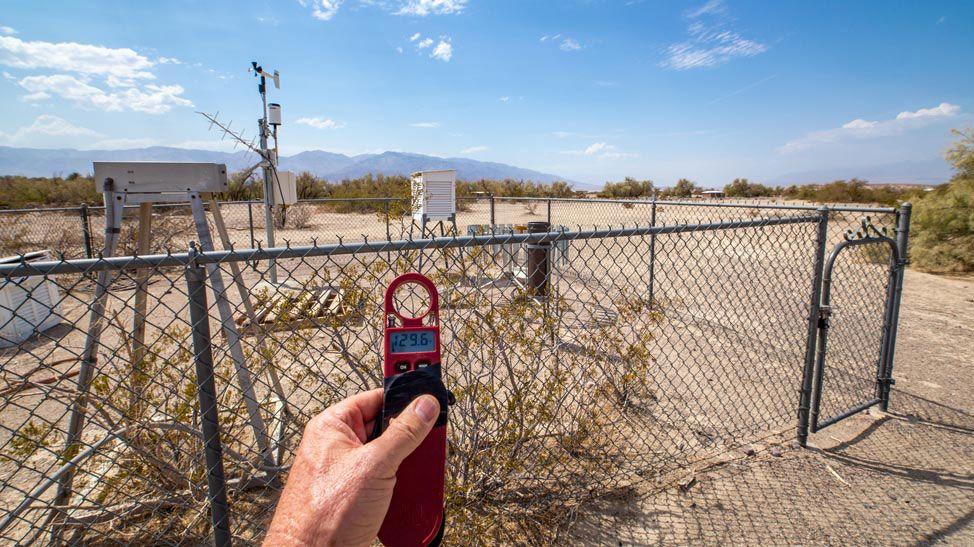 : Zdjęcie: stacja meteorologiczna w Dolinie Śmiercie. Widać otoczone płotem urządzenia pomiarowe, na pierwszym planie ręka z termometrem elektronicznym.]