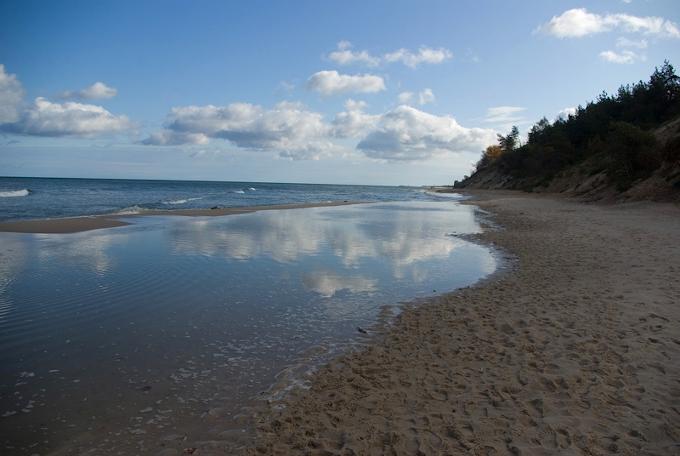 : Zdjęcie: wybrzeże morza we Władysławowie. Widać piaszczystą plażę, na której rozlana jest wielka kałuża wody, w której odbijają się chmury