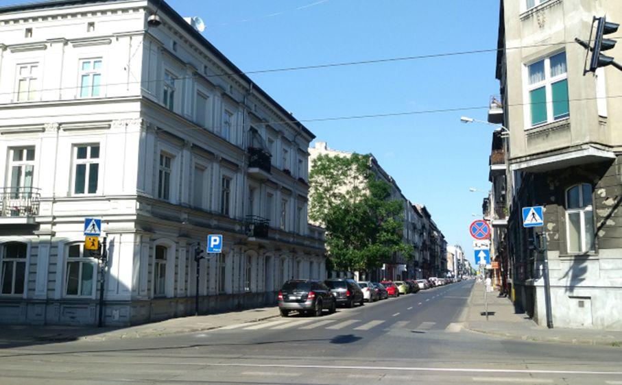 Zdjęcie: upał w Łodzi. Na zdjęciu miejska ulica zalana słońcem, wysokie kamienice, rząd zaparkowanych samochodów