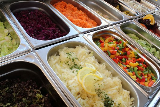 Zdjęcie: zbliżenie na pojemniki z surówkami, m.in. kiszona kapusta, tarta marchewka, mieszanka kolorowych papryk.