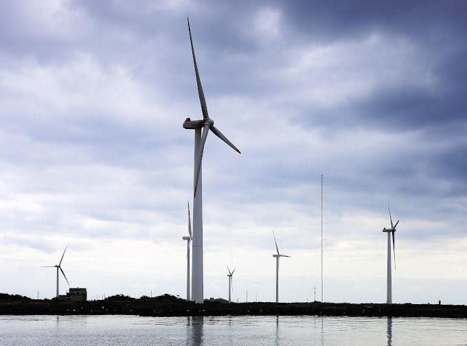 Zdjęcie: farma wiatrowa w Korei, wysokie wiatraki na brzegu morza.