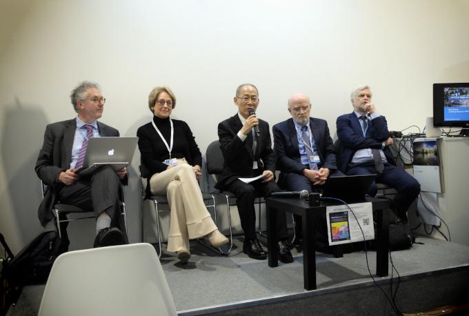 Zdjęcie: Przedstawiciele IPCC: czerech mężczyzna i jedna kobieta w średnim wieku, w strojach formalnych, siedzi na podwyższeniu. Prof. Hoesung Lee mówi do mikrofonu.