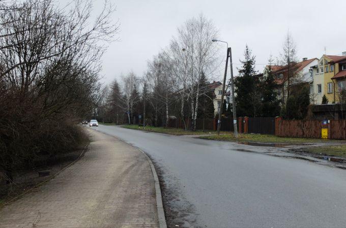 : Zdjęcie: luty 2018 w Warszawie. Widać zakręcającą ulicę, po prawej stronie domy jednorodzinne, trawniki i kałuże, po prawej szare krzaki. Śniegu brak.