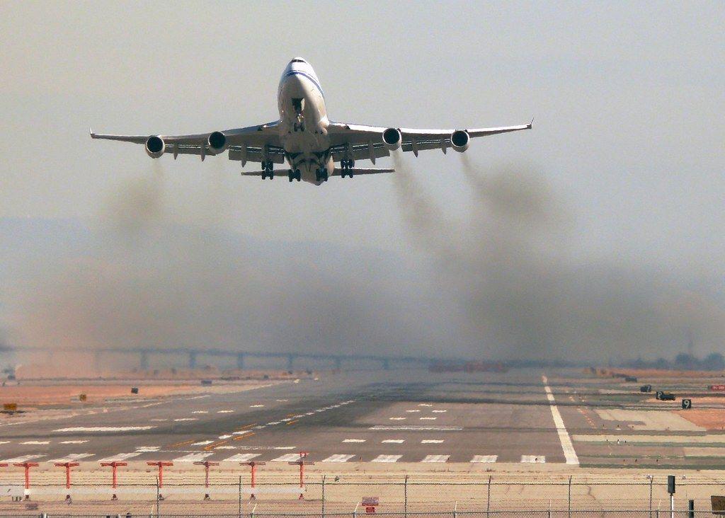 Zdjęcie: startujący samolot nisko nad pasem startowym, widziany od przodu.