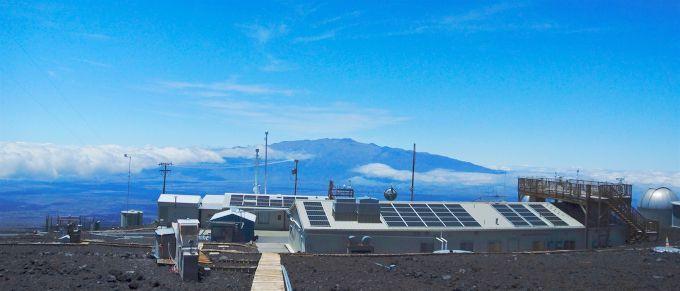 Zdjęcie: Obserwatorium Mauna Loa. Widać niskie zabudowania z bateriami słonecznymi na dachu, maszty z przyrządami, w tle góra i chmury.