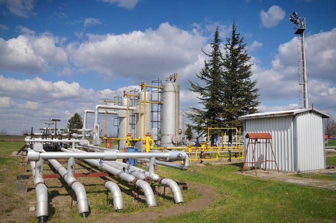 Zdjęcie: instalacja do przechowywania gazu, widać trzy duże zbiorniki i równe rzędy poziomych rur pośrodku pola.