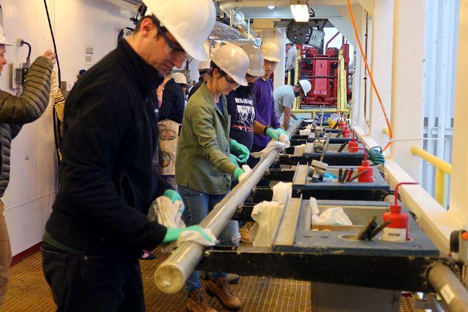 Zdjęcie: prace na statku badawczym. Pod pokładem, grupa ludzi w kaskach trzyma długi, cylindryczny obiekt i układa go na specjalistycznych podstawach