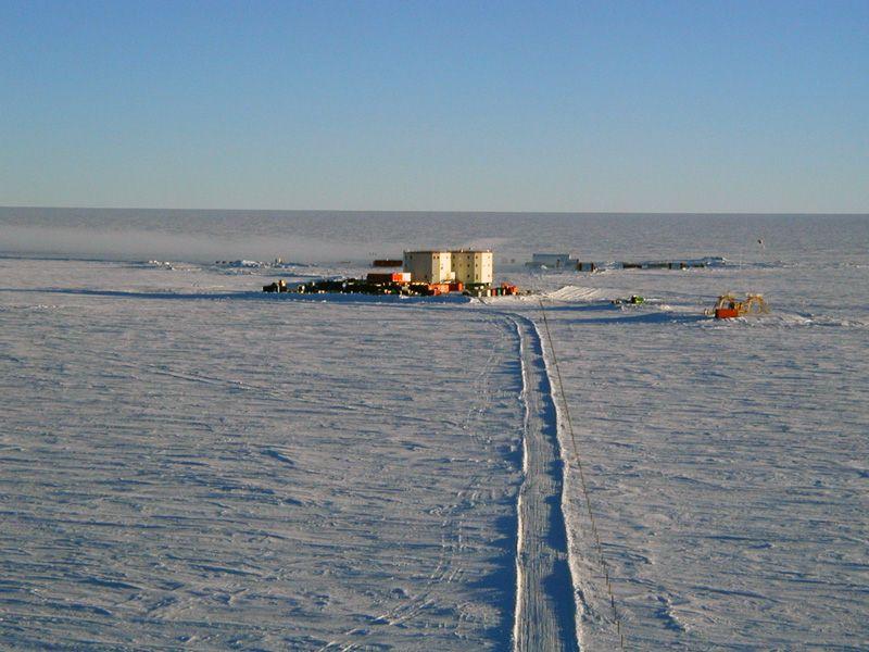 Zdjęcie: stacja Concordia, płaski, lodowy krajobraz, pośrodku baraki i dwa cylindryczne budynki kilkupiętrowe.