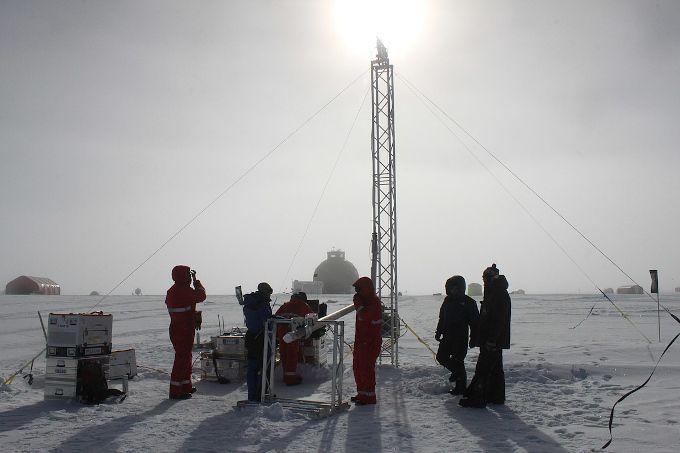 Zdjęcie: lodowa równina, grupa ludzi stoi wokół masztu kratownicowego, pośrodku podwieszony poziomo fragment wiertła z wydobytym rdzeniem, w tle niewielkie baraki.