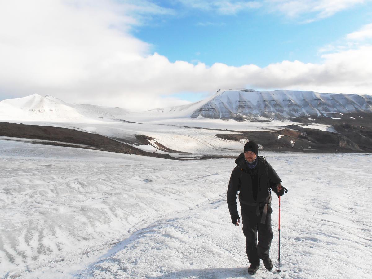 Zdjęcie: Jakub Małecki w zimowym stroju turystycznym, z plecakiem i tyczką na lodowcu – nieregularnej, białej powierzchni, w tle góry i chmury.