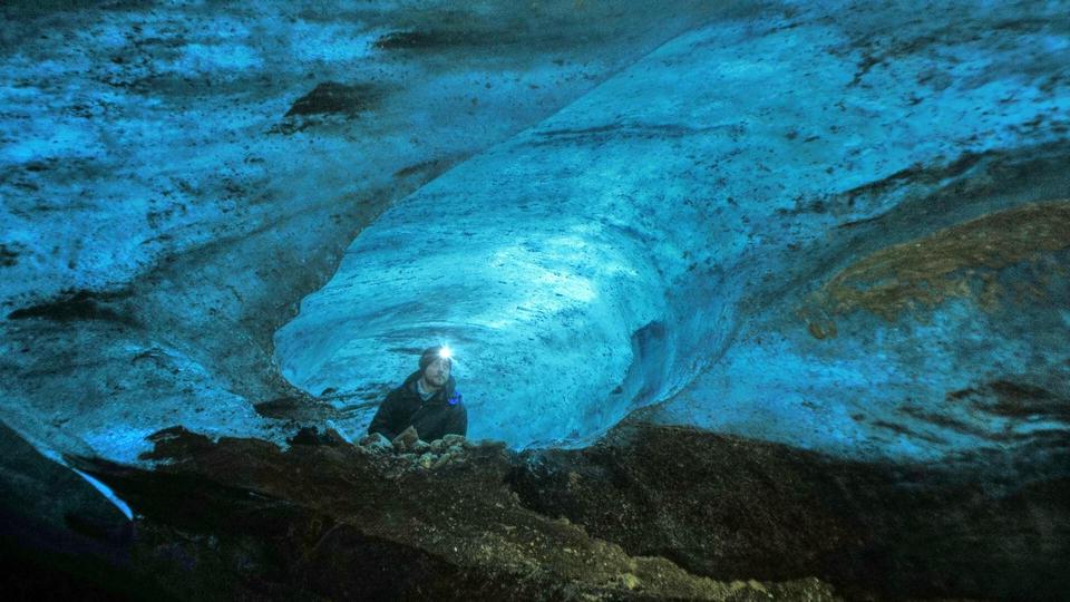 Zdjęcie: Jakub Małecki w zagłębieniu lodowca, zmrok rośzświetla latarka - czołówka.