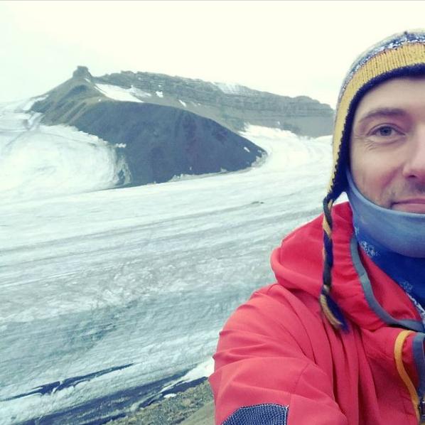 Zdjęcie: Jakub Małecki - selfie z lodowcem, widać pół popiersia autora i jęzor lodowca w tle.
