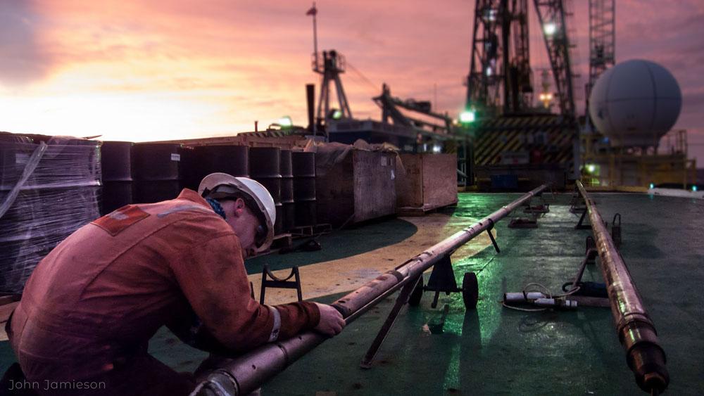 Zdjęcie: pokład statku, w lewym dolnym rogu mężczyzna w kasku i kombinezonie pochylony nad leżącymi na pokładzie, bardzo długimi, cienkimi rurami. W tle podstawa masztu kratownicowego i kopułka radaru.