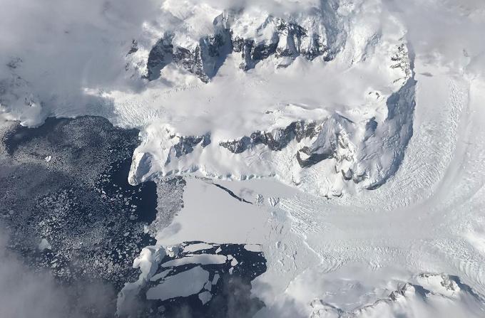 djęcie lotnicze lodowca Nobile, widać jęzor lodowca spływający pomiędzy górami do morza, oraz płaty lodu o różnych rozmiarach i grubościach (im dalej od wybrzeża, tym mniejsze i cieńsze).