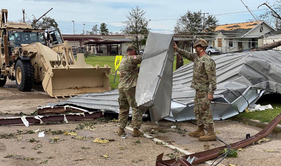 Zdjęcie: zniszczenia po przejściu huraganu, na trawniku i drodze między domami widać strzępy oderwanego, blaszanego dachu, nad jego usunięciem pracuje dwóch żołnierzy i spychacz.