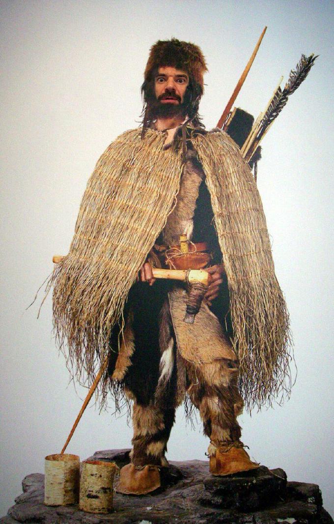 Zdjęcie: Ötzi – rekonstrukcja, figura o kształcie człowieka, z zarostem, w prymitywnym ubraniu i z bronią.